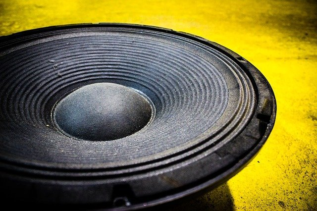 black round component speaker on a yellow background